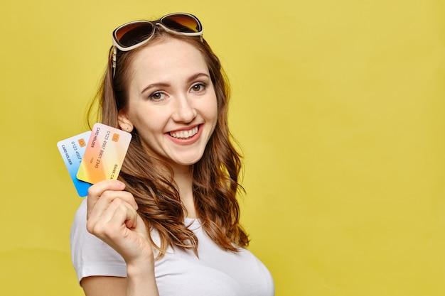 Chica muestra tarjetas de crédito como un concepto de préstamo de vacaciones.