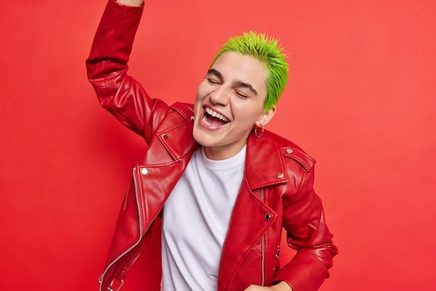 Chica se mueve con el ritmo de la música mantiene el brazo levantado expresa emociones positivas y sentimientos tontos vestidos con ropa de moda en rojo vivo