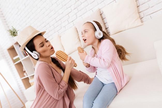 Chica y mujer en auriculares cantando en casa.