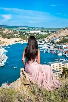 Chica, una mujer joven sentada al borde de un acantilado. verano de la bahía de balaklava en tiempo soleado.