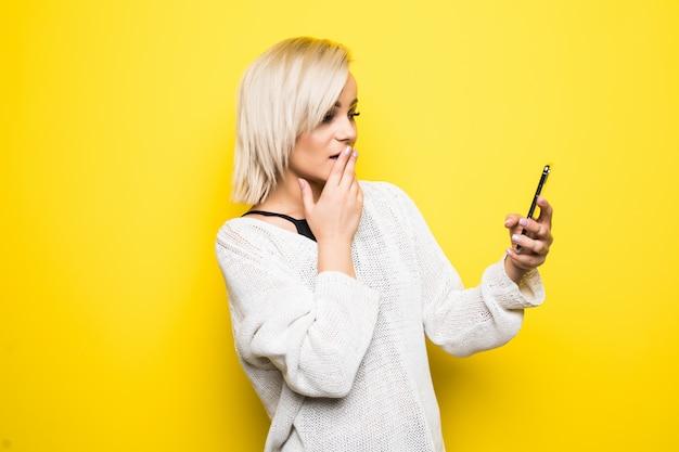 Chica de mujer joven en suéter blanco utiliza smartphone en amarillo