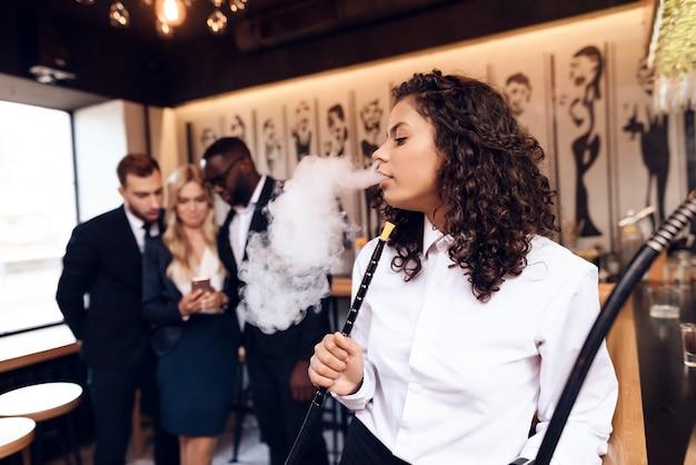 Chica mulata está fumando un narguile en el bar.