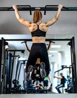 Chica musculosa, atlética, culturista en ropa deportiva tirando hacia arriba en una barra horizontal frente al espejo en el gimnasio.