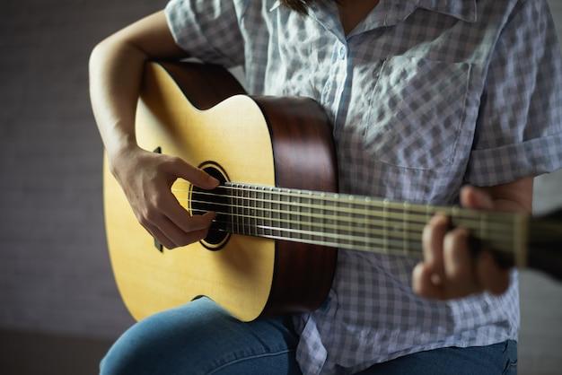 Chica músico tocando la guitarra acústica