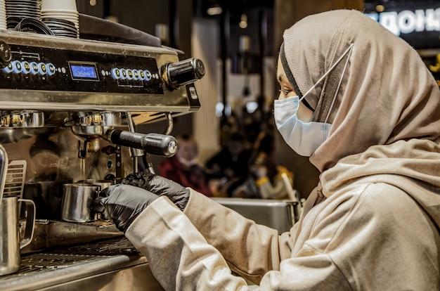 Chica musulmana con la cabeza cubierta, máscara médica y guantes está preparando café en el centro comercial de la cafetería.