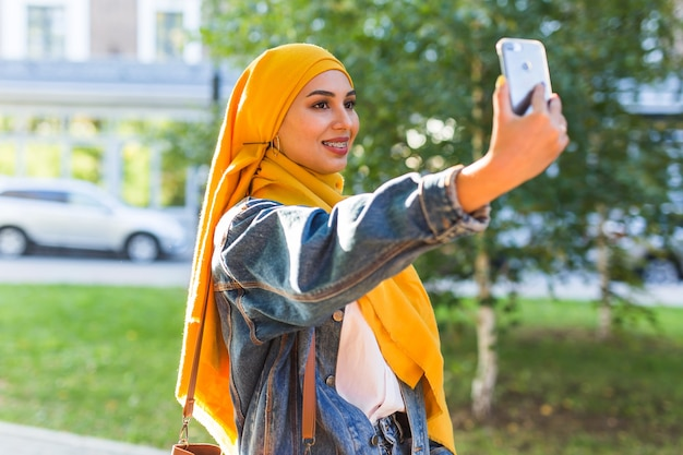 Chica musulmana con hijab hace un selfie en el teléfono de pie en la calle de la ciudad