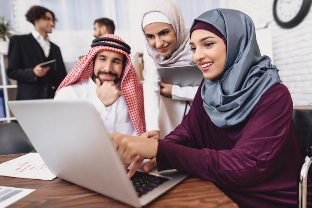 Chica musulmana muestra datos sobre planificación financiera de pc.