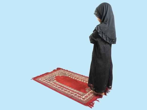 Chica musulmana en un vestido rezando