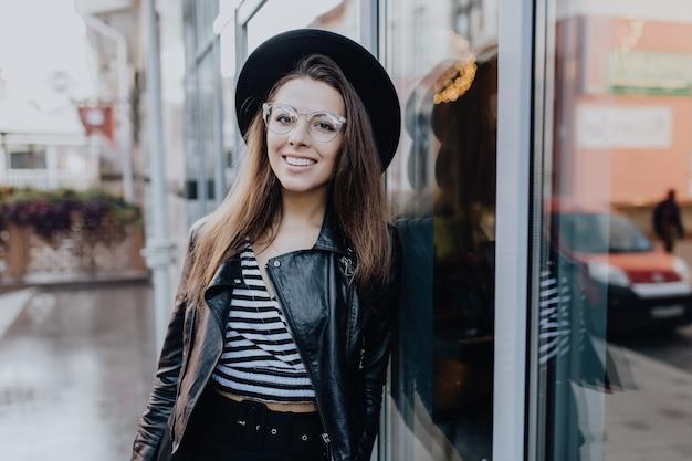 Chica muy elegante camina por la calle en chaqueta de cuero negro después de la lluvia