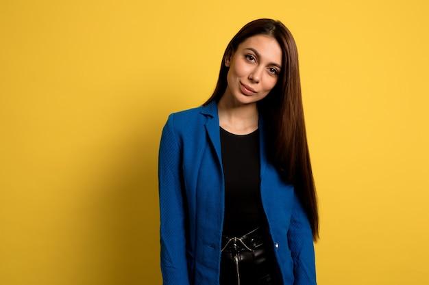 Chica muy elegante con maquillaje desnudo y cabello largo y oscuro durante la sesión de fotos sobre una pared aislada