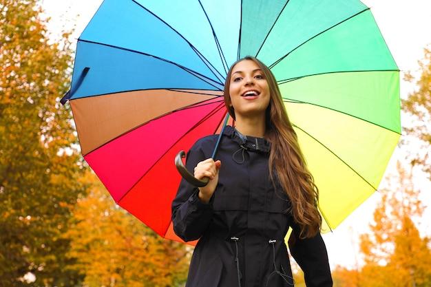 Chica muy hermosa bajo el paraguas de lluvia del arco iris en el parque