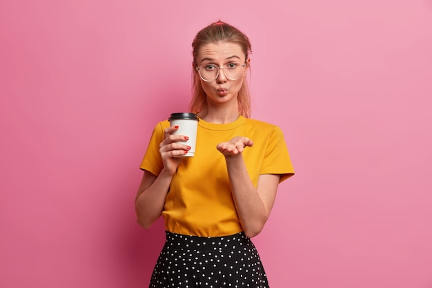 Una chica muy romántica solo envía amor, mantiene los labios redondeados, envía mwah, sostiene café para llevar, se viste de manera informal
