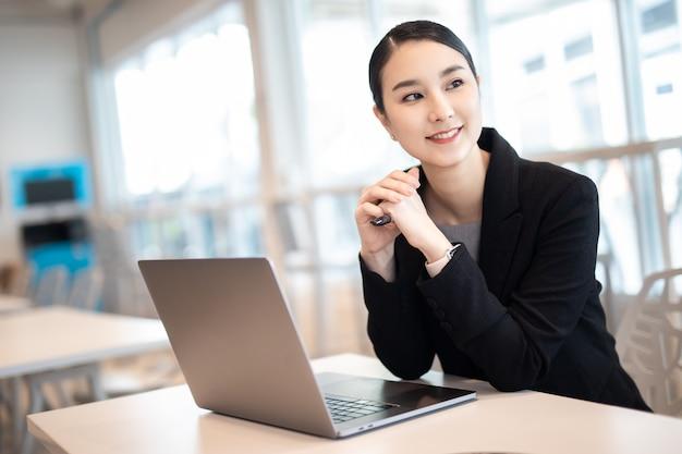 Chica de negocios asiática joven que trabaja con el portátil en la cafetería de la cafetería, sonriendo mirar hacia otro lado.