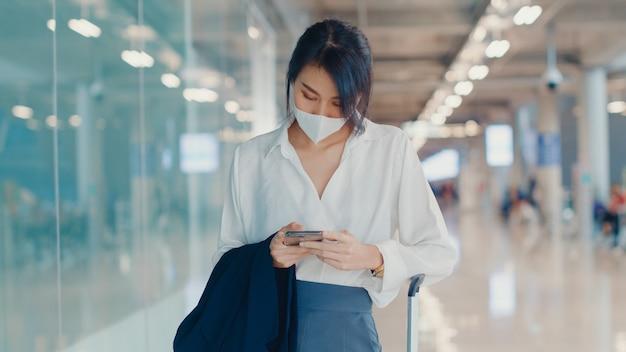 Chica de negocios asiática que usa el teléfono inteligente para verificar la tarjeta de embarque caminando con el equipaje a la terminal en el vuelo nacional en el aeropuerto.