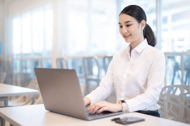 Chica de negocios asiáticos jóvenes trabajando con el portátil en la cafetería cafetería.