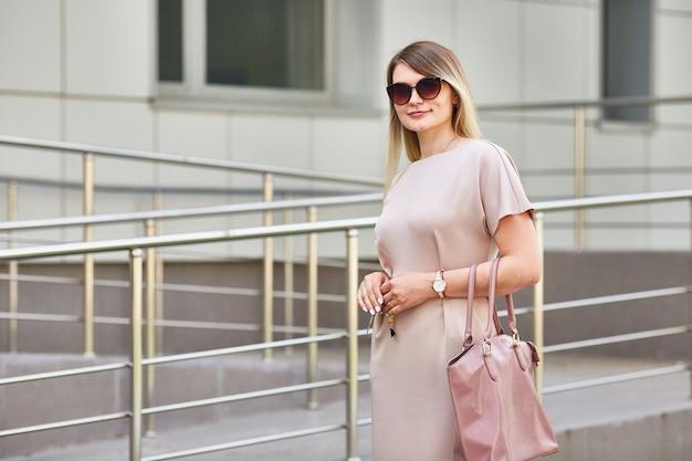 Chica de negocios en gafas de sol caminando por la calle