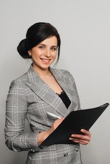 Chica de negocios en traje con una carpeta de documentos y una sonrisa amistosa.