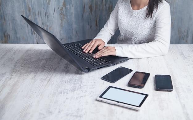 Chica de negocios usando la computadora portátil en la oficina.