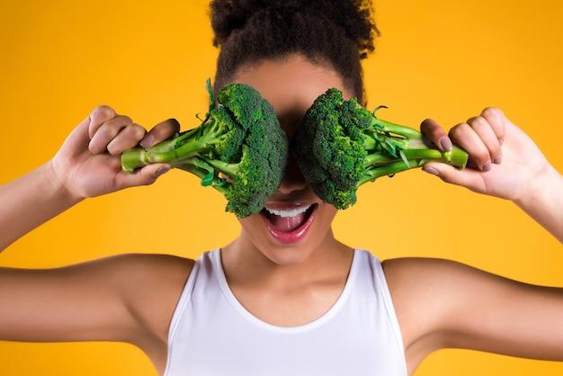 Chica negra cerró los ojos de brócoli.