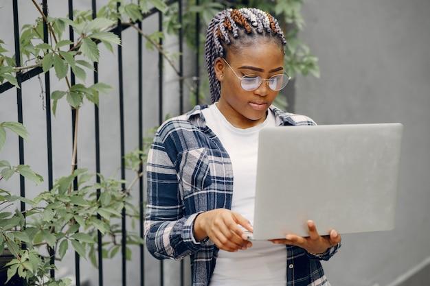 Chica negra en una ciudad de verano con laptop