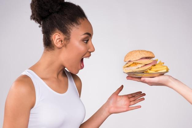 La chica negra está contenta con la hamburguesa con queso.