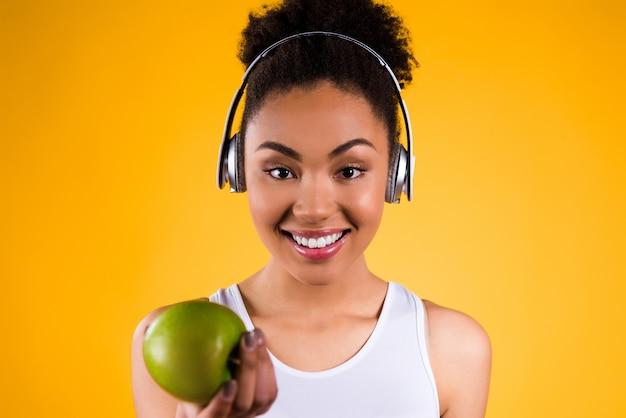 Chica negra da una manzana y sonríe