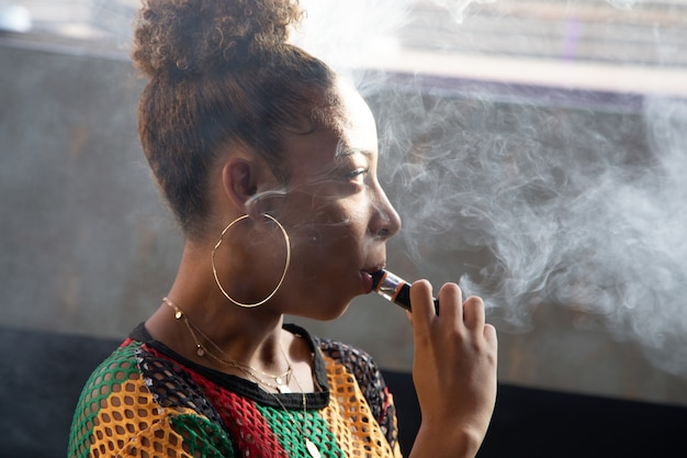 Chica negra fumando con un vapor mientras mira a un lado