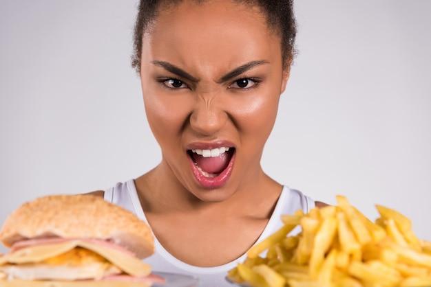 Chica negra gritando a hamburguesa y papas fritas.