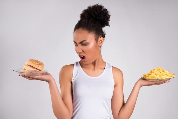 Chica negra con hamburguesa con queso y papas fritas aisladas