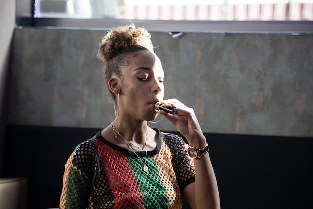 Chica negra inhalando un vapor