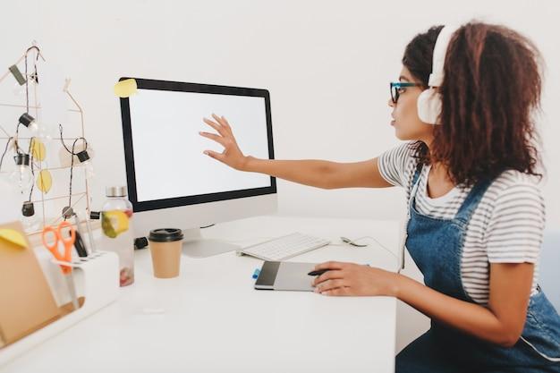 Chica negra en mezclilla sentada en la mesa con papelería y tocando la pantalla de la computadora