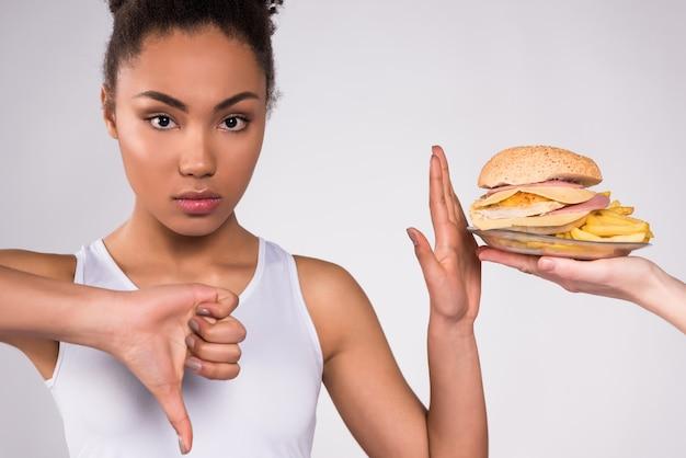 Chica negra puso su dedo en ellos muestra que la comida nociva.