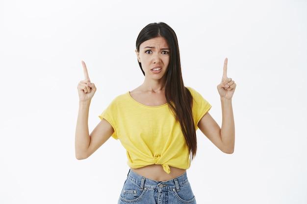 A la chica no le gusta lo que ve. mujer guapa incómoda y poco impresionada disgustada en camiseta amarilla levantando las manos apuntando hacia arriba