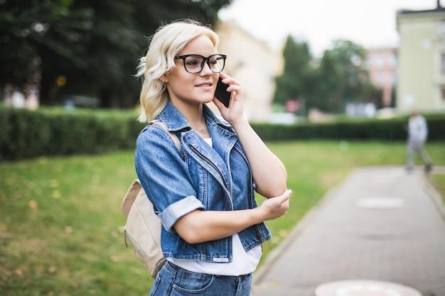Chica ocupada joven rubia usa el teléfono para desplazarse por la conversación de la red social en la mañana de la plaza otoño de la ciudad