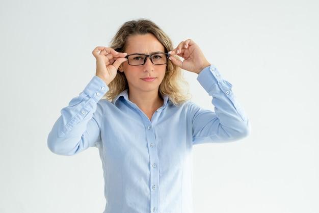 Chica de oficina ceñuda enfocada mirando a la cámara