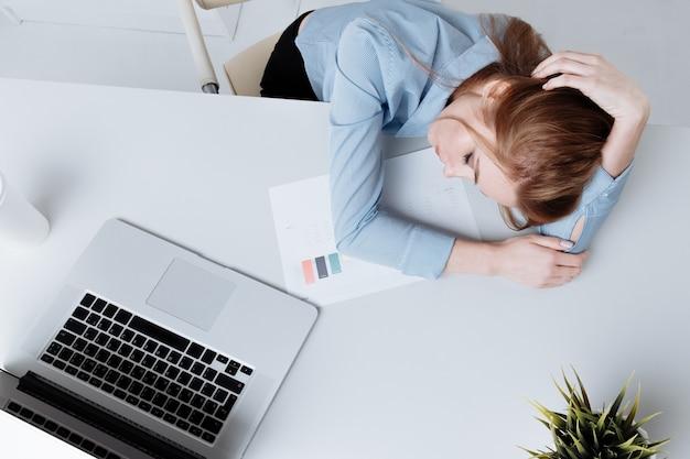 Chica de oficina joven sentada en su lugar de trabajo sintiéndose mal. la mujer tiene dolor de cabeza. parece cansado.