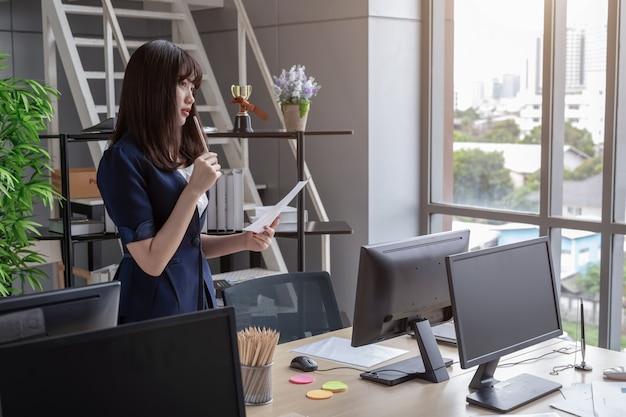 La chica de la oficina está de pie mirando el archivo del documento
