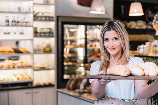 Chica ofreciendo bandeja de pan