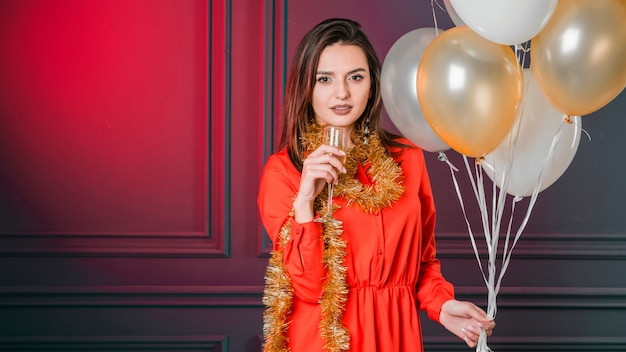 Chica ofreciendo champán con globos
