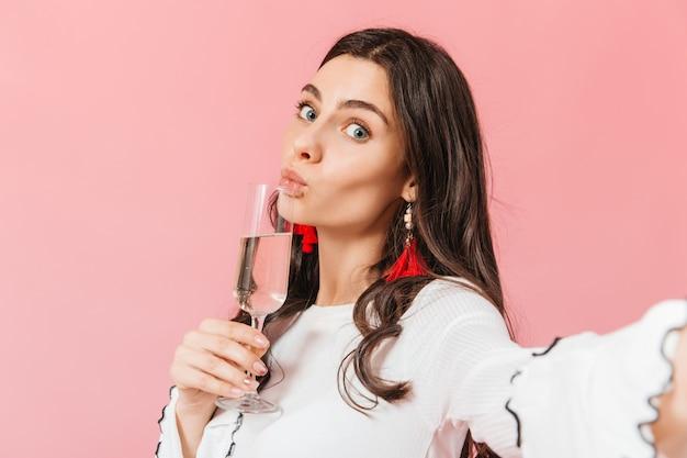 Chica de ojos azules hace selfie sobre fondo rosa con copa de vino espumoso.