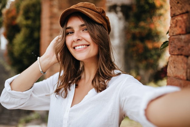 Chica de ojos marrones con gorra de terciopelo y blusa blanca hace selfie en el espacio de la pared de ladrillo y los árboles.