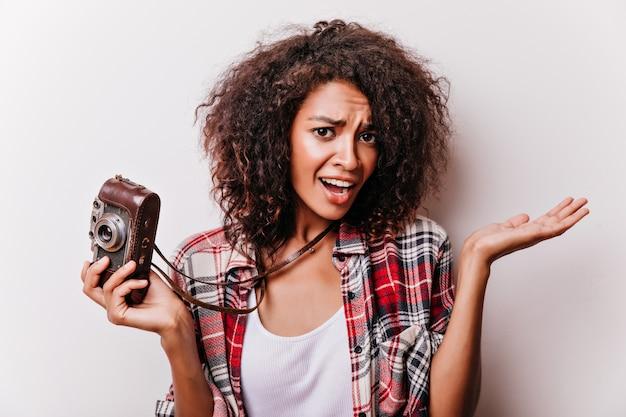 Chica de ojos oscuros con pie de cámara vintage en blanco. mujer rizada de moda posando después del trabajo.