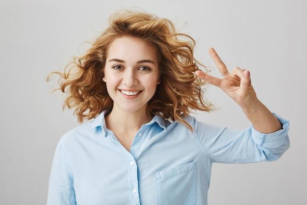 Chica optimista despreocupada con cabello rizado mostrando el signo de la paz y sonriendo