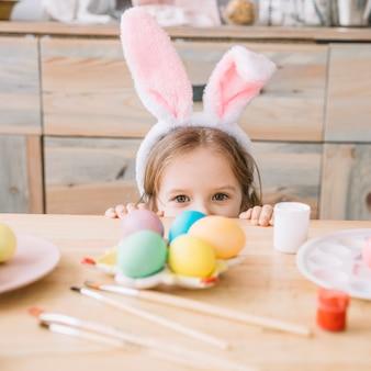 Chica en orejas de conejo escondida detrás de la mesa con huevos de pascua