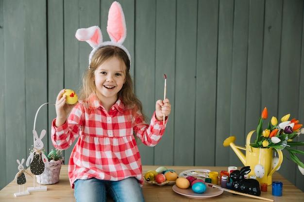 Chica en orejas de conejo pintando huevo para pascua