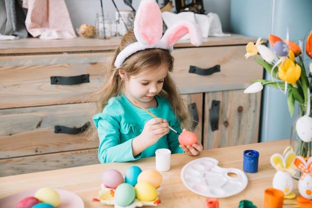Chica en orejas de conejo pintando huevos para pascua