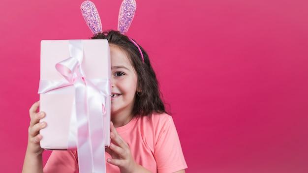Chica en orejas de conejo que cubre la cara con caja de regalo