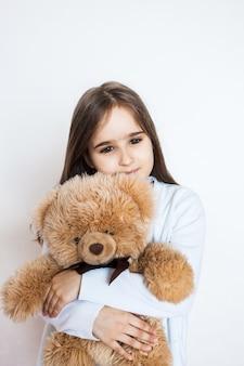 Chica con un oso de peluche favorito, infancia y cuidado, familia y amigos. niña jugando y abrazando juguete