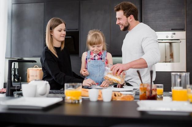 Chica con padres preparando el desayuno