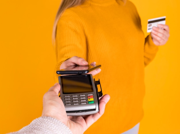 Chica pagando con tarjeta de crédito, comprando en línea desde su teléfono inteligente, pared amarilla